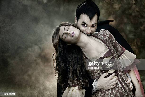 Vampire sucking blood from woman's neck