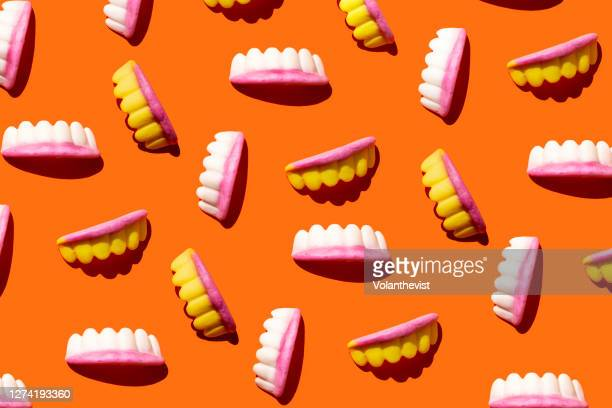 vampire teeth halloween jelly beans pattern on orange background - halloween stock pictures, royalty-free photos & images
