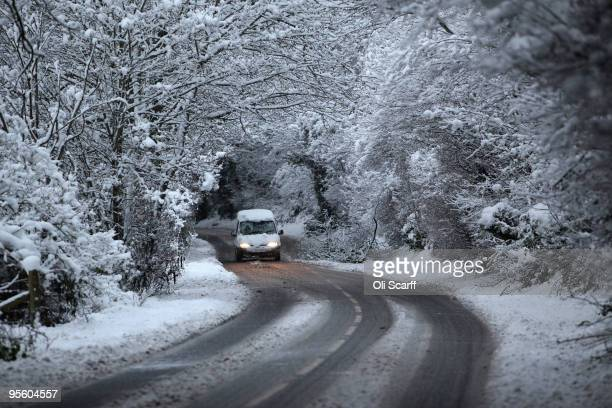 A van avoids a fallen tree as it travels along a snowlined road on January 6 2010 in HenleyonThames England The MET Office has put in place severe...