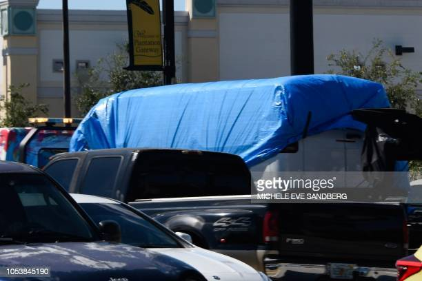 A van covered in blue tarp is towed by FBI investigators on October 26 in Plantation Florida in connection with the 12 pipe bombs and suspicious...