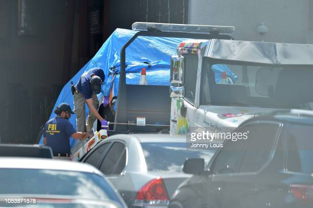 A van covered in blue tarp is unloaded by FBI investigators at FBI Miramar Headquarters on October 26 2018 in Miramar Florida The van belongs to...