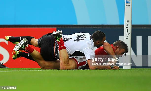 Van Der Merwe of Canada beats Madalin Lemnaru of Romania to score their first try during the 2015 Rugby World Cup Pool D match between Canada and...