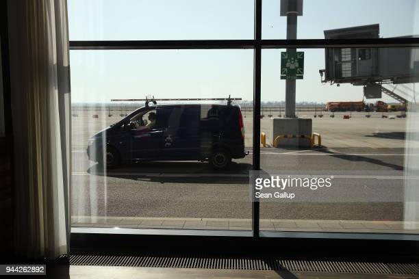 A van drives on the tarmac outside a departures lounge at the BER Willy Brandt Berlin Brandenburg International Airport on April 10 2018 in...