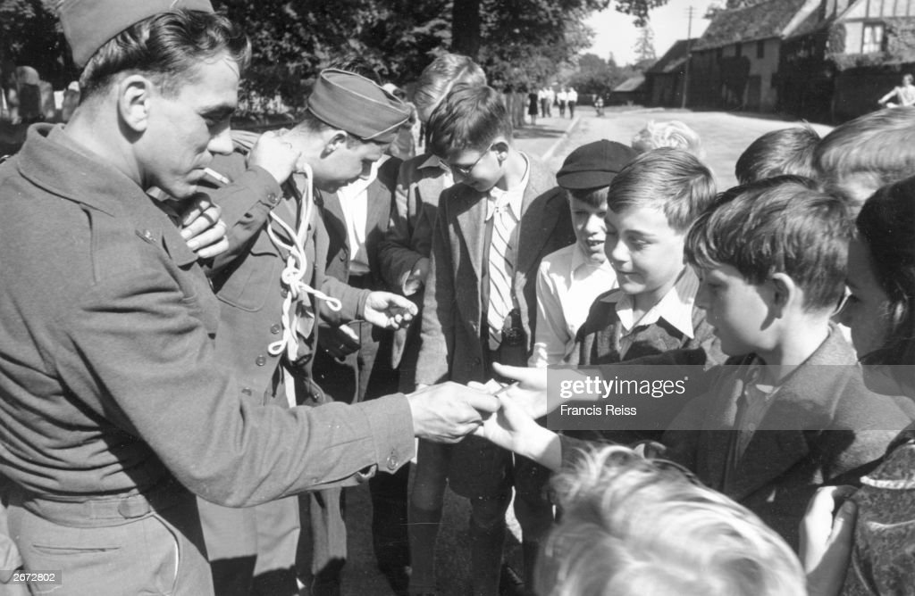Van Horne and Tetrault, two American soldiers, say goodbye and 'gum, chum?' to Buckden village children with their last sticks of chewing gum. Original Publication: Picture Post - 2091- Two American Soldiers Say Goodbye In East Anglia - pub. 1945