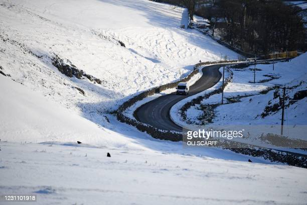 Van is driven along a road between snow-covered fields in the countryside near Tideswell in The Peak District in northern England on February 11 as...