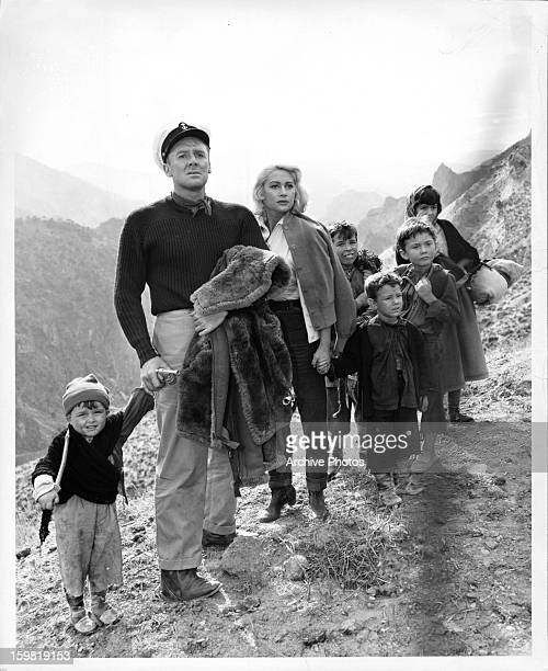 Van Johnson and Martine Carol holding the hands of children on a mountainside in a scene from the film 'Action Of The Tiger' 1957
