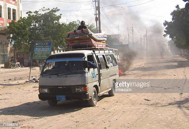 A van loaded with mattresses and residents of Mogadishu leaving the city drives past a burning barricade 28 October 2007 Hundreds of families fled...