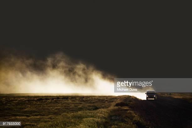 Van on dirt road creating dust