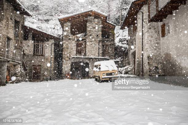 van parking in a square facing old houses of the village under a heavy snowfall. - italia stock-fotos und bilder