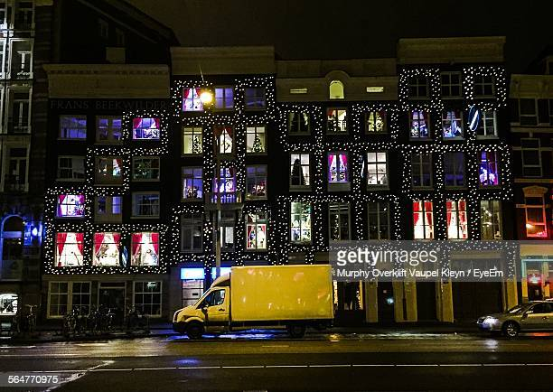 Van Passing By Illuminated Building During Christmas