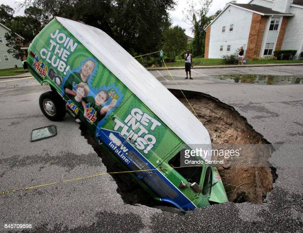 A van remains in a sinkhole on Monday Sept 11 2017 that opened up at the Astor Park apartment complex in Winter Springs Fla during Hurricane Irma's...