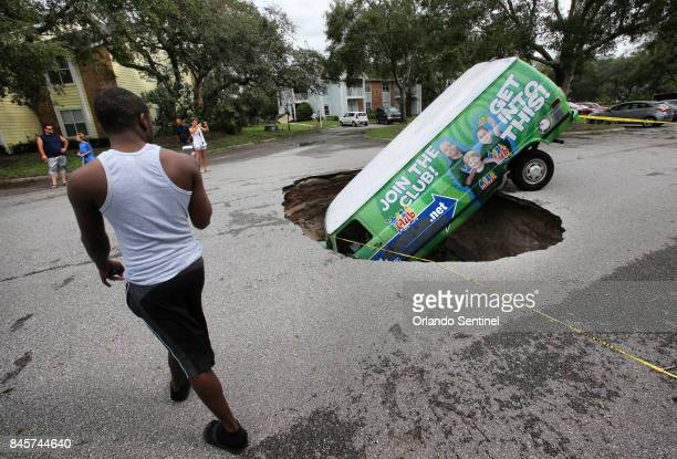A van remains in a sinkhole on Monday Sept 11 that opened up at the Astor Park apartment complex in Winter Springs Fla during Hurricane Irma's...