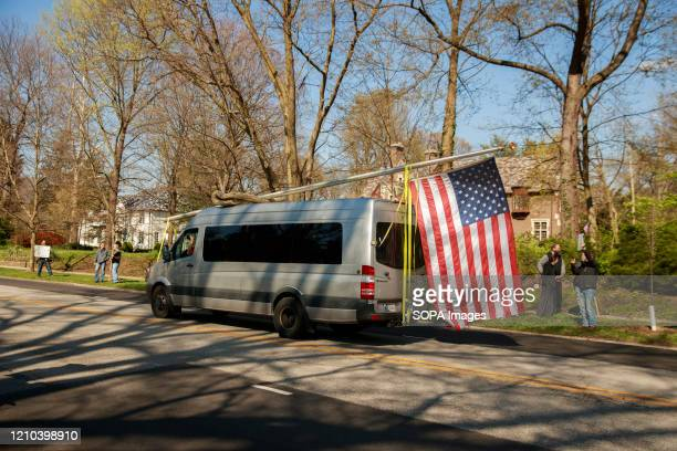 Van with an American flag drives on the street during the protest. Protesters gather outside Indiana Governor Eric Holcomb's mansion in the 4700...