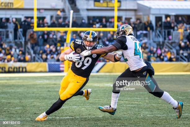 Vance McDonald of the Pittsburgh Steelers fends off Barry Church of the Jacksonville Jaguars during the third quarter of the AFC Divisional Playoff...