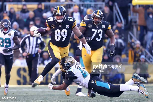 Vance McDonald of the Pittsburgh Steelers jumps over Barry Church of the Jacksonville Jaguars during the second half of the AFC Divisional Playoff...