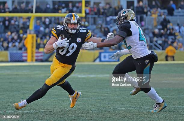 Vance McDonald of the Pittsburgh Steelers stiff arms Barry Church of the Jacksonville Jaguars after a reception in the third quarter during the AFC...