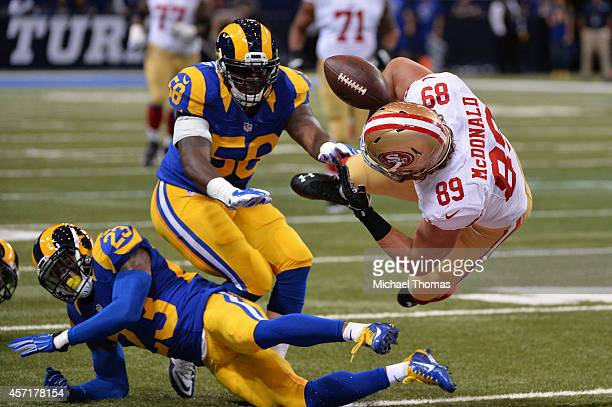 Vance McDonald of the San Francisco 49ers fumbles the ball as he is tackled by Rodney McLeod and JoLonn Dunbar of the St Louis Rams in the first...
