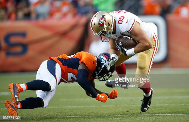 Vance McDonald of the San Francisco 49ers gets hit after making a reception during the game against the Denver Broncos at Sports Authority Field on...