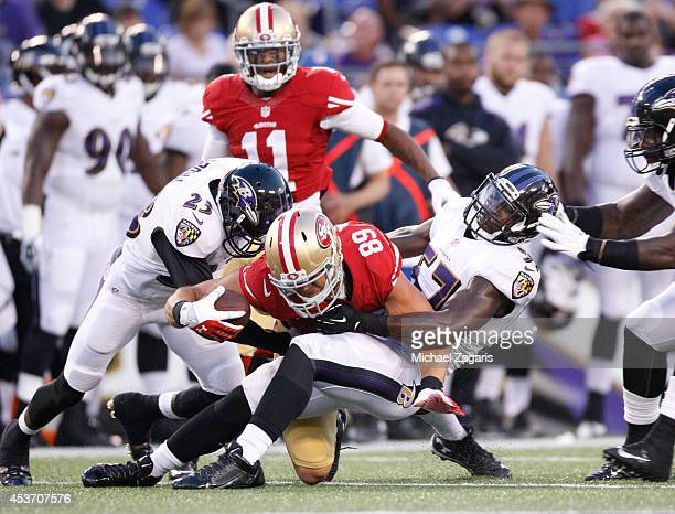 Vance McDonald of the San Francisco 49ers is tackled by CJ Mosley and Chykie Brown of the Baltimore Ravens during the game at MT Bank Stadium on...