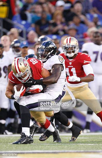 Vance McDonald of the San Francisco 49ers is tackled by CJ Mosley of the Baltimore Ravens during the game at MT Bank Stadium on August 7 2014 in...