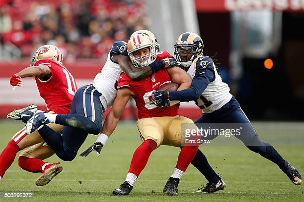 Vance McDonald of the San Francisco 49ers is tackled by Janoris Jenkins and Maurice Alexander of the St Louis Rams during their NFL game at Levi's...