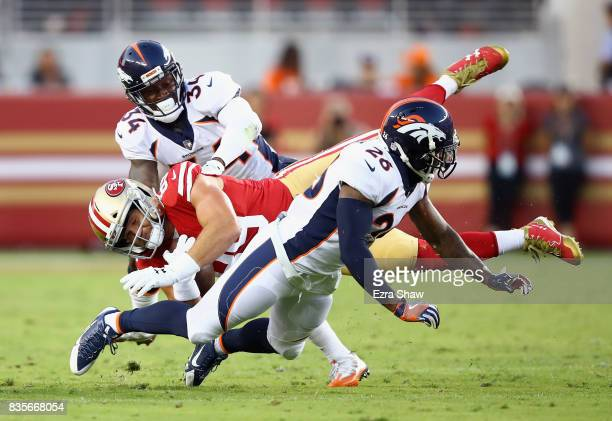Vance McDonald of the San Francisco 49ers is tackled by Will Parks and Darian Stewart of the Denver Broncos at Levi's Stadium on August 19 2017 in...