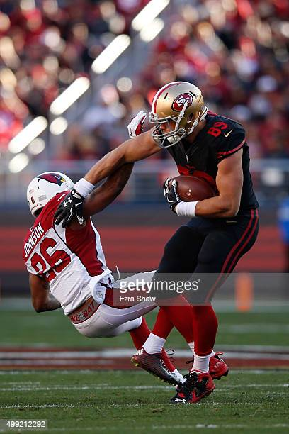 Vance McDonald of the San Francisco 49ers knocks down Rashad Johnson of the Arizona Cardinals after making a catch during their NFL game at Levi's...
