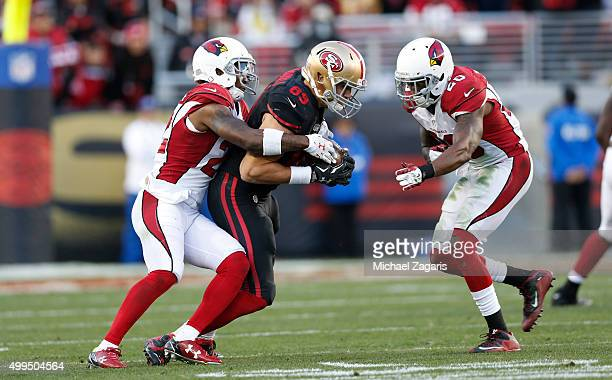 Vance McDonald of the San Francisco 49ers makes a reception as Tony Jefferson and Deone Bucannon of the Arizona Cardinals close in during the game at...