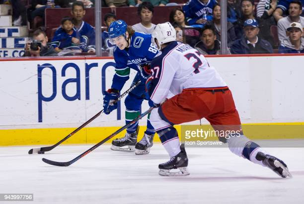 VANCOUVER BC MARCH 31 Vancouver Canucks Center Adam Gaudette handles the puck behind Columbus Blue Jackets Defenceman Ryan Murray during the third...