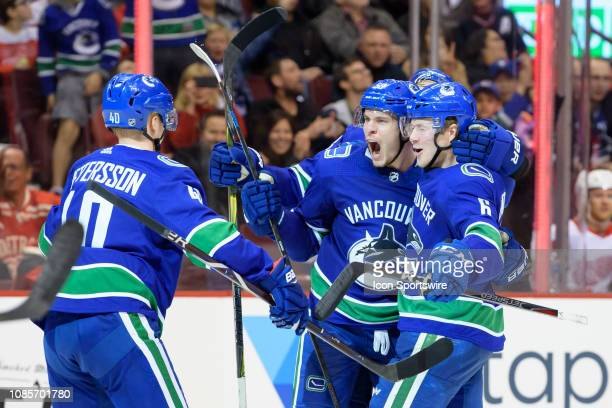 Vancouver Canucks Center Bo Horvat is congratulated by Center Elias Pettersson and Right wing Brock Boeser after scoring a goal against the Detroit...