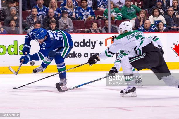 Vancouver Canucks Center Bo Horvat takes a shot on net as Dallas Stars Defenceman John Klingberg defends during their NHL game at Rogers Arena on...