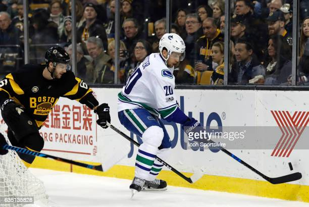 Vancouver Canucks center Brandon Sutter tries to control the puck as Boston Bruins right defenseman Colin Miller rushes in during a regular season...