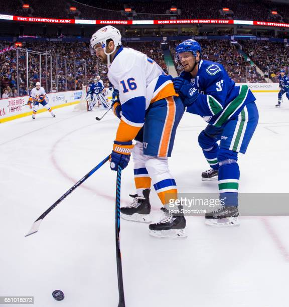 Vancouver Canucks Center Henrik Sedin checks New York Islanders Left Wing Andrew Ladd during a NHL hockey game on March 09 at Rogers Arena in...