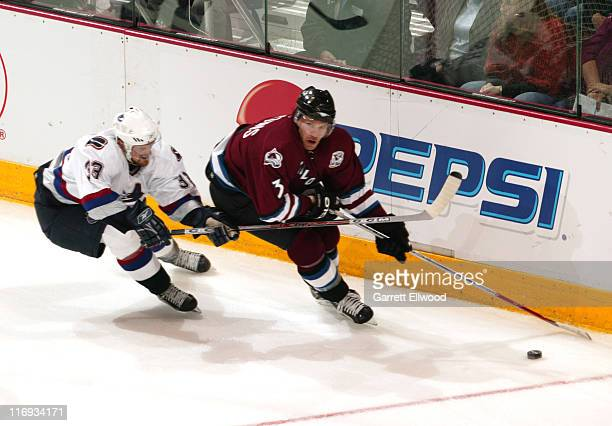 Vancouver Canucks center Henrik Sedin fights for the puck with Colorado Avalanche defenseman Karlis Skrastins during the game between the Vancouver...