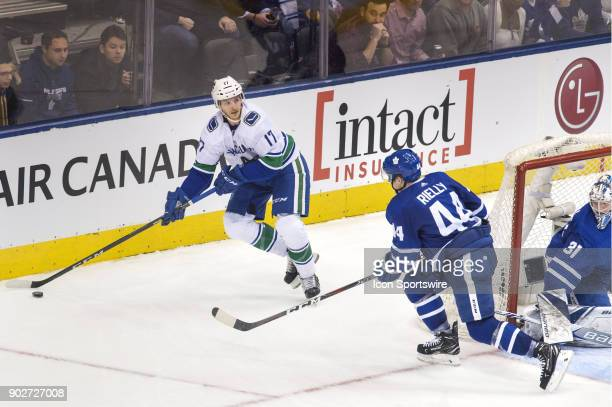 Vancouver Canucks Center Nic Dowd prepares to pass the puck as Toronto Maple Leafs Defenceman Morgan Rielly pursues behind the Leafs net during the...