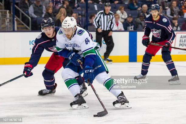 Vancouver Canucks center Tyler Motte controls the puck as Columbus Blue Jackets defenseman Zach Werenski pursues in a game between the Columbus Blue...