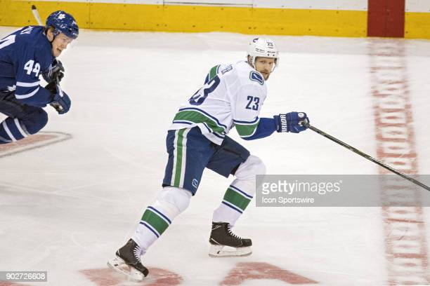 Vancouver Canucks Defenceman Alexander Edler is pursued by Toronto Maple Leafs Defenceman Morgan Rielly during the regular season NHL game between...
