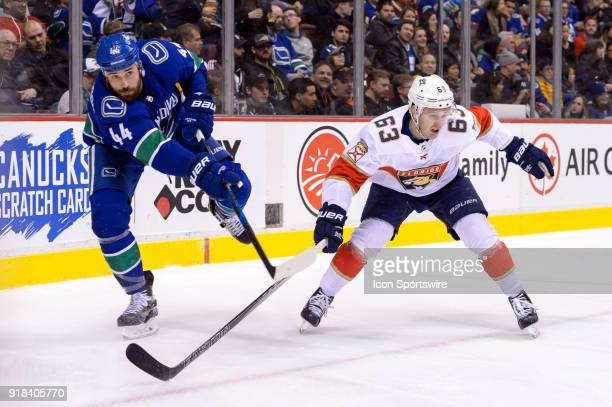 Vancouver Canucks Defenceman Erik Gudbranson shoots the puck ahead of Florida Panthers Left Wing Evgenii Dadonov during their NHL game at Rogers...