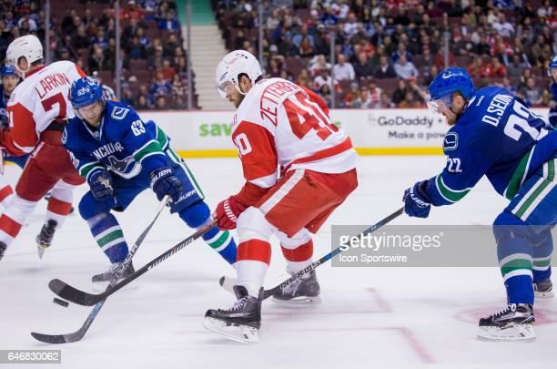 Vancouver Canucks Defenceman Philip Larsen and Left Wing Daniel Sedin check Detroit Red Wings Center Henrik Zetterberg during a NHL hockey game on...