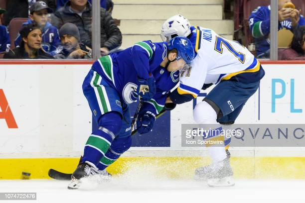 Vancouver Canucks Defenseman Ben Hutton and St Louis Blues Left Wing Jordan Nolan battle for the puck during their NHL game at Rogers Arena on...
