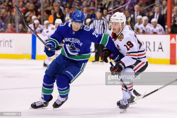 Vancouver Canucks defenseman Ben Hutton battles for position with Chicago Blackhawks Center Jonathan Toews during their NHL game at Rogers Arena on...