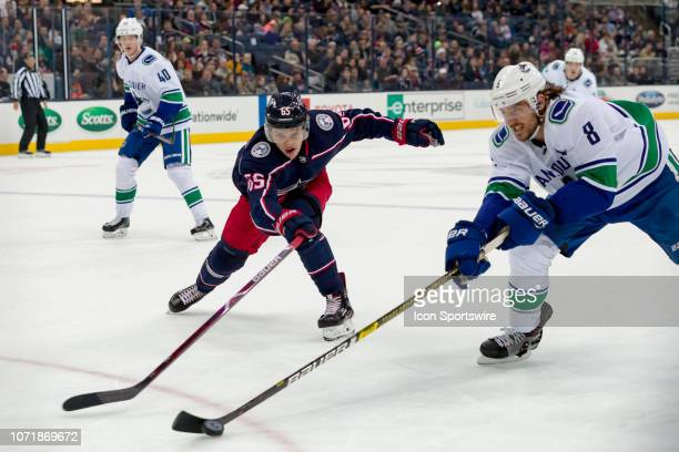 Vancouver Canucks defenseman Christopher Tanev and Columbus Blue Jackets defenseman Markus Nutivaara battle for the puck in a game between the...