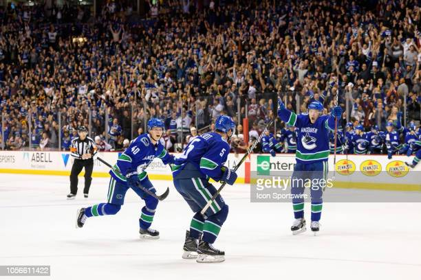 Vancouver Canucks defenseman Derrick Pouliot celebrates with right wing Brock Boeser and center Elias Pettersson after scoring a goal in overtime...