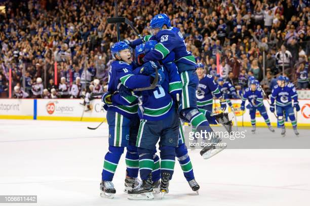 Vancouver Canucks defenseman Derrick Pouliot celebrates with right wing Brock Boeser center Bo Horvat and center Elias Pettersson after scoring a...