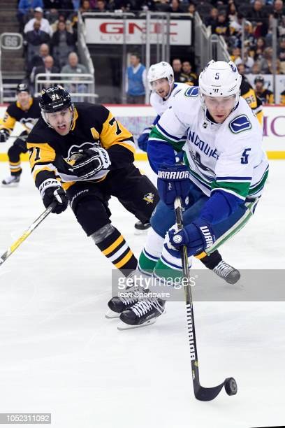 Vancouver Canucks Defenseman Derrick Pouliot plays the puck under pressure from Pittsburgh Penguins Center Evgeni Malkin during the first period in...