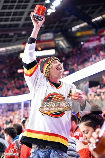 Vancouver Canucks fan celebrates a goal during the first period of an NHL game where the Calgary Flames hosted the Vancouver Canucks on December 29...