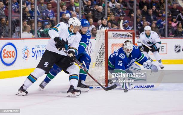 Vancouver Canucks Goalie Jacob Markstrom makes a save as Defenseman Alexander Edler checks San Jose Sharks Left Wing Evander Kane during the first...