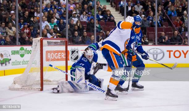 Vancouver Canucks Goalie Jacob Markstrom makes a save behind New York Islanders Left Wing Anders Lee and Vancouver Canucks Cefenseman Alexander Edler...