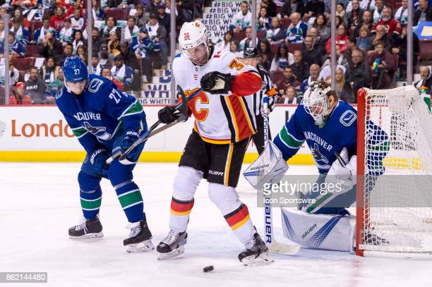 Vancouver Canucks Goalie Jacob Markstrom watches the puck as Vancouver Canucks Defenceman Ben Hutton defends against Calgary Flames Right Wing Troy...