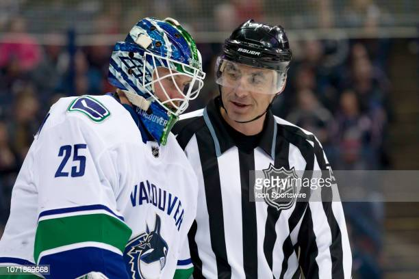 Vancouver Canucks goaltender Jacob Markstrom chats with linesman Derek Amell as he skates back to the bench in a game between the Columbus Blue...